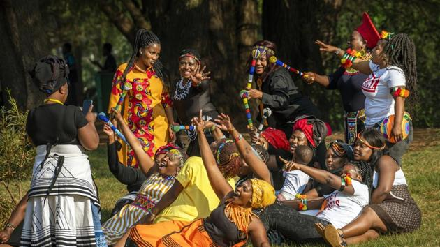 A group of women dressed in traditional clothing pose for a selfie as they celebrate South Africa's Heritage Day at Zoo Lake park in Johannesburg.(AP)