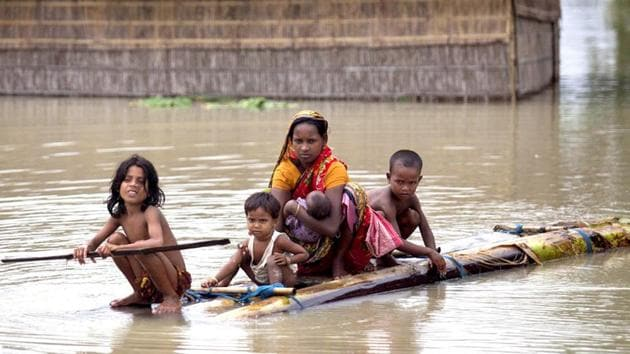 Flood affected people use rafts made of banana trunks to move to safer places at Mayong in Morigaon district of Assam.(PTI)