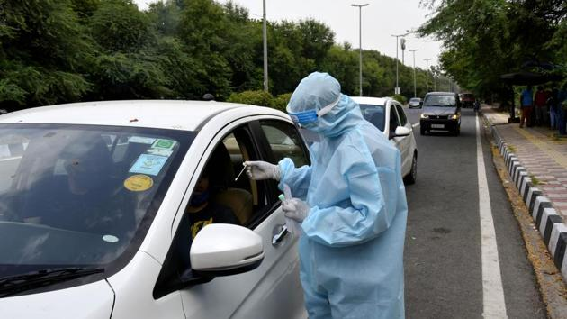 A healthcare worker takes a swab for RT-PCR based coronavirus testing at a paid drive through centre at Aruna Asaf Ali Marg, in New Delhi on Saturday.(Vipin Kumar/HT Photo)