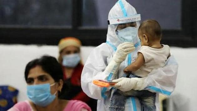 A medical worker in personal protective equipment (PPE) plays with the child of a woman recovering inside a quarantine centre from the coronavirus disease in New Delhi.(REUTERS PHOTO.)
