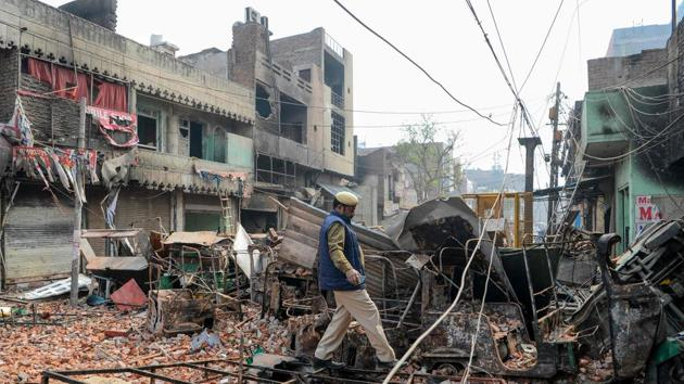 In this file photo taken on February 26, 2020, a Delhi police personnel patrols near burnt-out and damaged residential premises and shops following clashes between people supporting and opposing a contentious amendment to India's citizenship law, New Delhi(AFP)