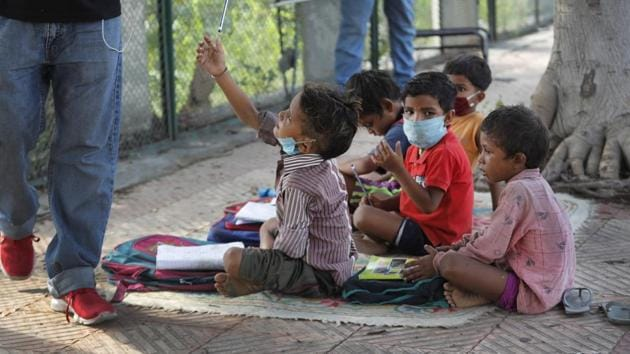A child takes a pencil during a class conducted by a former diplomat Virendra Gupta and his singer wife Veena Gupta on a sidewalk in New Delhi on Sept. 3, 2020.(AP Photo)