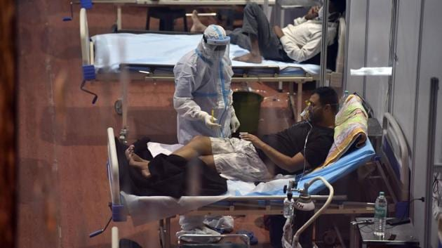 A health worker checks vitals of a Covid-19 patient inside a Covid Care Centre in New Delhi.(Sanjeev Verma/HT Photo)