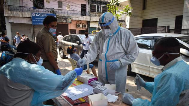 A health worker in PPE coveralls hands over a collected swab sample to colleagues during coronavirus testing, at Hudson Lane, in New Delhi on Sunday.(Sanchit Khanna/HT Photo)