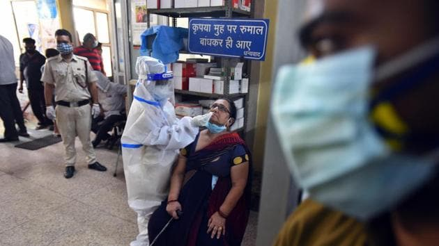 A health worker in PPE coveralls collects a swab sample from a person for coronavirus testing, at a government dispensary in New Delhi on September 28, 2020.(Raj K Raj/HT Photo)