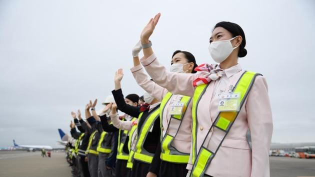 Japan Airlines Co. (JAL) employees wearing protective masks wave to see off a Boeing 767-300ER aircraft at Narita Airport in Narita, Japan on Saturday.(Bloomberg File Photo)