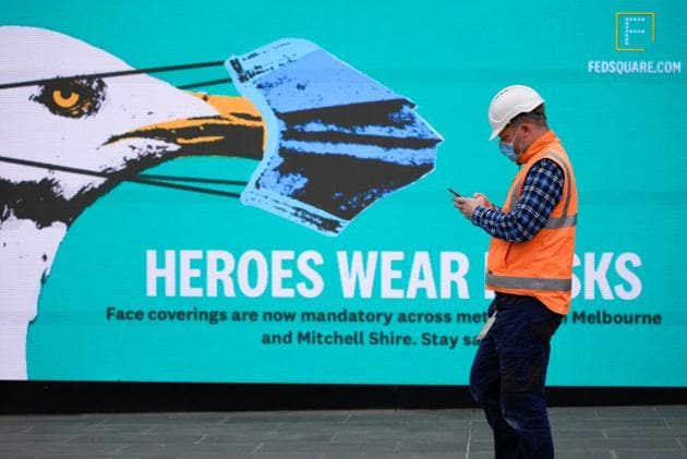 An essential worker wearing a face mask walks past a 'Heroes Wear Masks' sign in Melbourne after it became the first city in Australia to enforce mask-wearing in public as part of efforts to curb a resurgence of the coronavirus disease (Covid-19), July 23, 2020. REUTERS/Sandra Sanders/Files