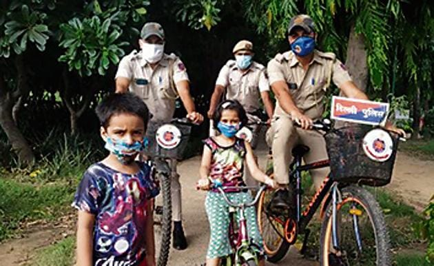 Kids take picture with Delhi Police cops patrolling on their bicycles in Nehru Park.