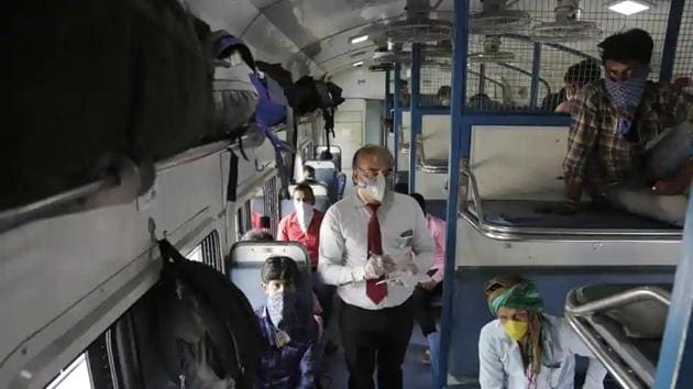 A ticket collector checks the tickets of migrant workers siting inside a special train to return to Agra in Uttar Pradesh state.(AP File Photo)