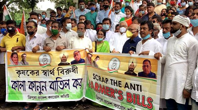 Congress supporters hold a banner and raise slogans as they protest against the new farm bills in Agartala on Monday.(ANI)