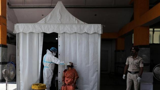 A healthcare worker wearing personal protective equipment (PPE) collects a swab sample from a woman, amid the spread of the coronavirus disease (Covid-19), in New Delhi.(Reuters)
