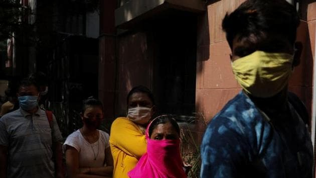 People wearing protective face masks wait in line to get tested for the coronavirus disease (Covid-19), in New Delhi.(Reuters)