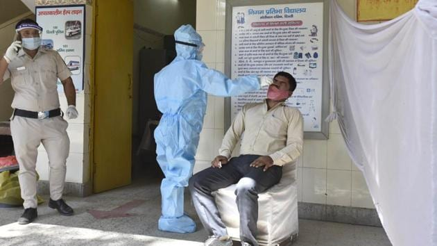 A healthcare worker collects a swab sample from a person for coronavirus testing, in New Delhi's South Moti Bagh on Monday.(Sanjeev Verma/HT Photo)