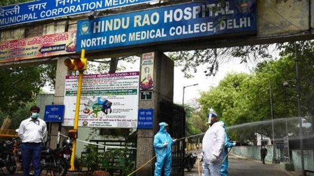 New Delhi Municipal Council (NDMC) workers spray disinfectant during the sanitization of the Hindu Rao Hospital.(Vipin Kumar/HT File Photo)