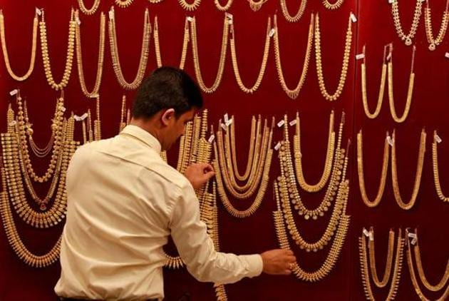 A salesman arranges gold ornaments on a display board inside a jewellery showroom in Kochi in this file phtoto.(Reuters Photo)