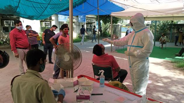 A health worker wearing Personal Protective Equipment (PPE) gives a nasal swab to a person for a rapid-antigen methodology Covid-19 test at Sarai Kale Khan Transport Authority in New Delhi on Monday.(Bloomberg Photo)