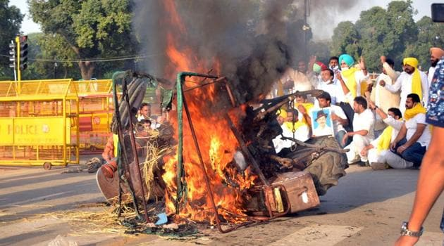 A tractor set on fire by Punjab Youth Congress Workers (PYCW) to protest the passing of agriculture reform bills by the President, at India Gate in New Delhi on Monday.(HT Photo)