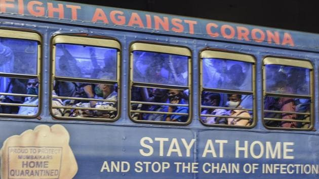 Commuters in Mumbai travel in a crowded bus which is carrying a message urging people to stay at home to fight the spread of Covid-19.(PTI)