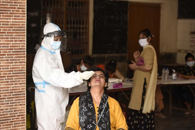 A health worker collecting a swab sample at Bhagwati Vidya Mandir School in Madanpuri, Gurugram, on Tuesday.(Parveen Kumar/HT)