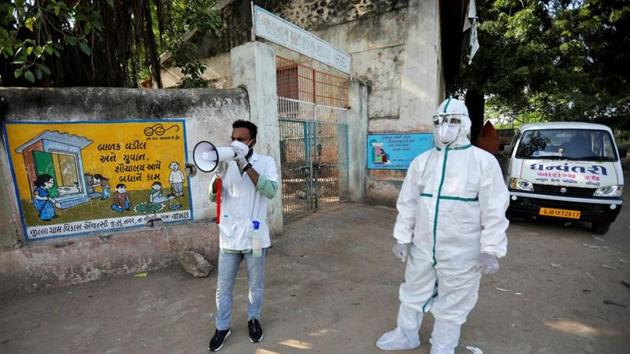 A healthcare worker announces to people to get their rapid antigen tests done during a door-to-door survey for the coronavirus disease (COVID-19), in Jakhan village in the western state of Gujarat.(REUTERS)
