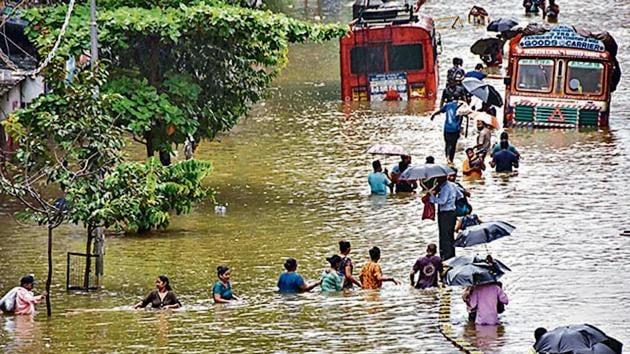 People wade through a waterlogged street at Parel area, after heavy monsoon rain, in Mumbai(PTI Photo)