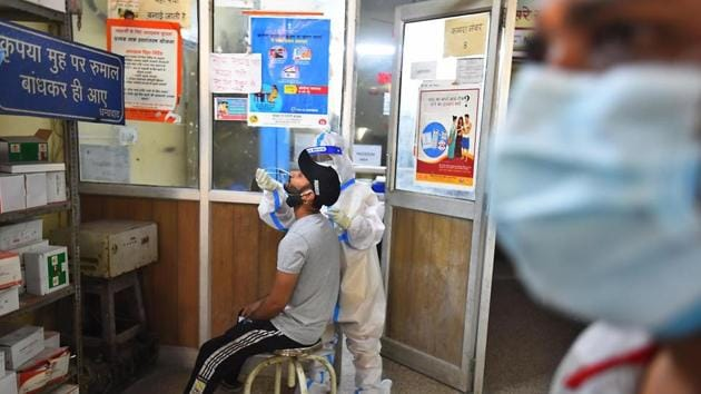 A health worker in PPE coveralls collects a swab sample from a person for coronavirus testing, at a government dispensary in New Delhi.(Raj K Raj/ Hindustan Times)