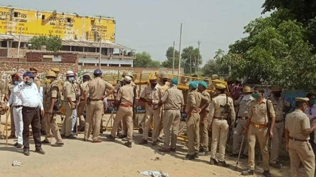 Police personnel stand guard at the entrance of Boolgarhi village where the family of 19-year-old Dalit woman who was gang-raped two weeks ago resides, in Hathras district of Uttar Pradesh.(PTI)