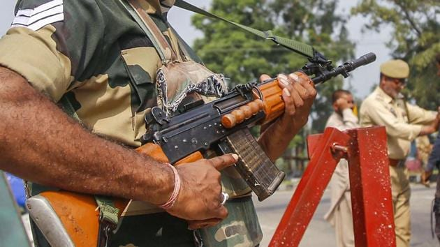 A BSF jawan guards as Jammu and Kashmir Police personnel check the vehicles on the Jammu-Srinagar highway after a truck was seized with arms and ammunition, in Kathua.(PTI)