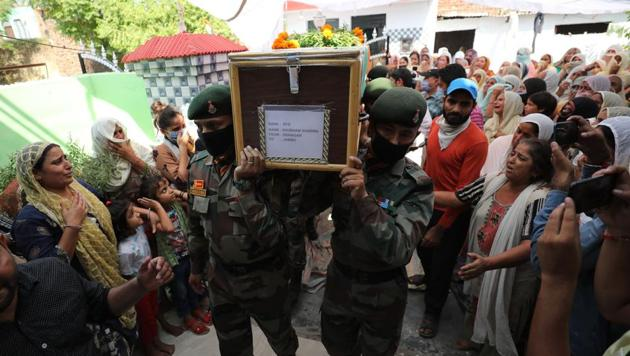 Army officials carry the coffin of soldier Shubham Sharma at his native village in RS Pura sector of Jammu on Friday.(HT photo)