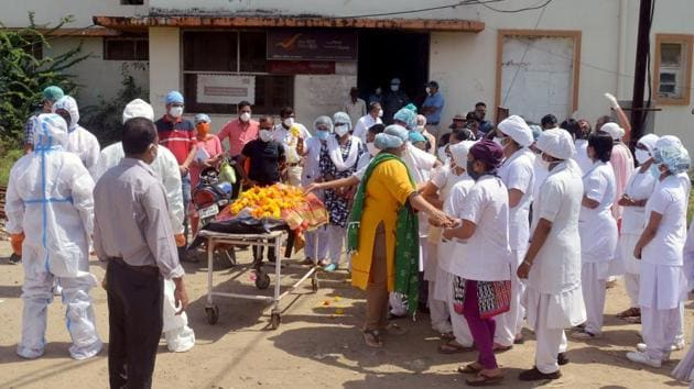 Medical staff at the cremation centre with the body of a staff nurse from Netaji Subhash Chandra Bose Medical College who died from Covid-19, in Jabalpur, Madhya Pradesh, on Thursday.(ANI)