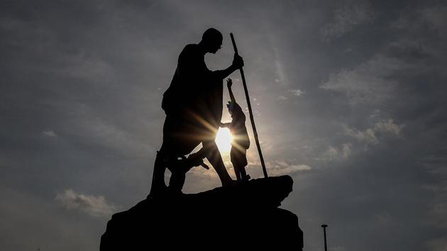 A worker cleans Mahatama Gandhi statue on the eve of his birth anniversary at Marinabeach, in Chennai.(PTI)