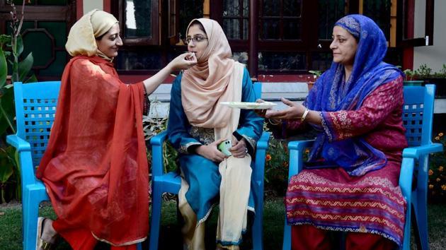 J&K civil services examination topper Kamila Mushtaq 's sister offers her sweets in Srinagar on Thursday.(ANI)