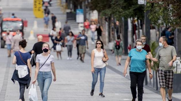 People wear face masks as they walk along a street in Montreal, Canada.(AP)