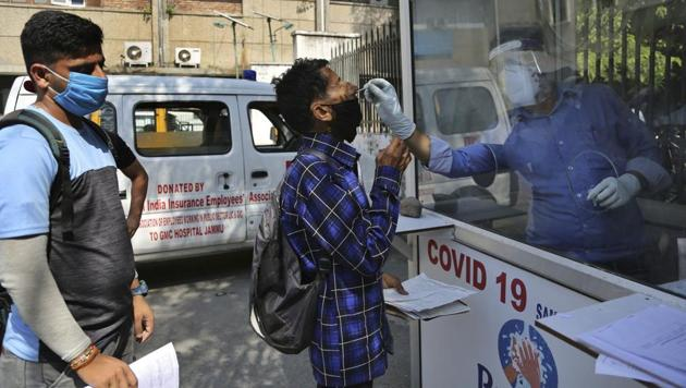 A health worker collects a man's swab sample to test for Covid-19 at a government hospital in Jammu on Thursday.(AP)