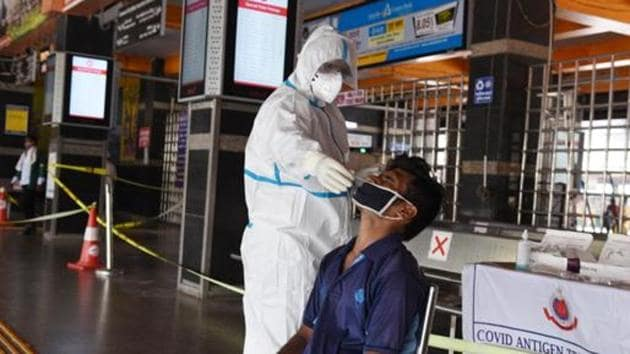 A health worker in a PPE kit collects a swab sample from an Indian railways employee for a rapid antigen Covid-19 test at New Delhi Railway Station.(HT PHOTO.)