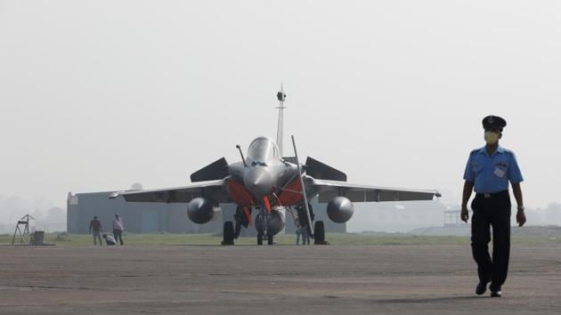 An Indian Air Force officer wearing a protective face mask walks in front of a Rafale fighter jet during its induction ceremony at an air force station in Ambala, India, September 10, 2020.(REUTERS)