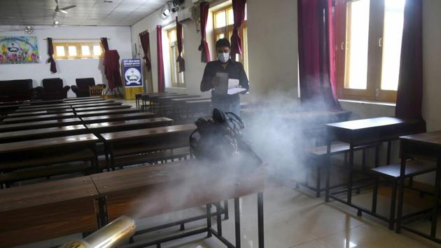 An MCD employee sprays disinfectant inside a classroom after a staffer was tested positive for Covid-19, at a school in Srinagar.(PTI)