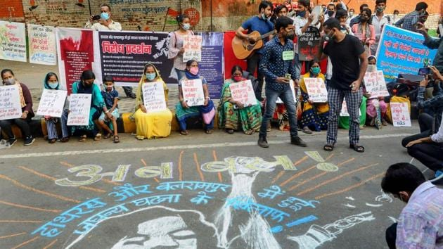 Demonstrators hold placards and stand near a mural on a street as they protest against the alleged gang-rape of a 19-year-old Dalit woman in Hathras (UP) in New Delhi on Sunday.(PTI Photo)