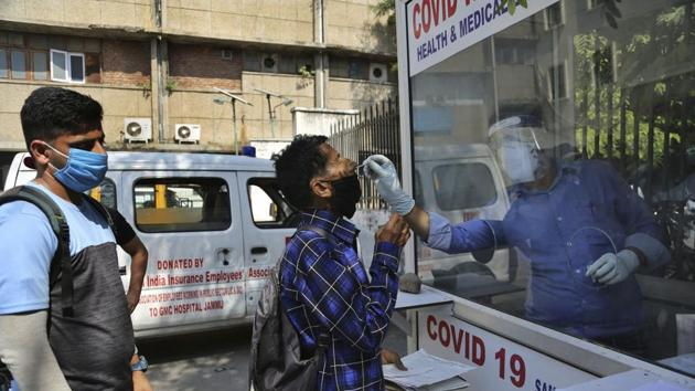 A health worker collects a man's swab sample at a government hospital in Jammu.(AP)