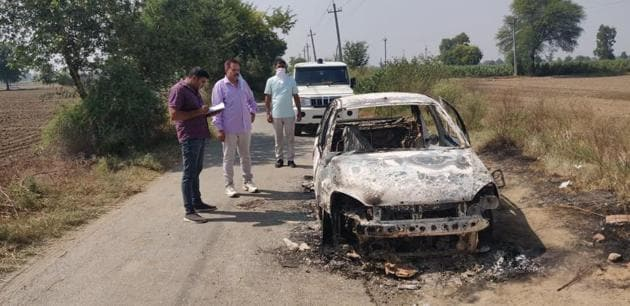 Investigators at the site where the car of the trader was burnt near Bhatla village at Hansi in Hisar on Tuesday night.(HT Photo)