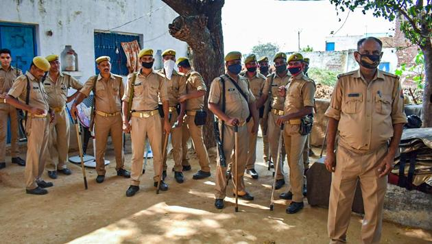 Police personnel stand guard outside the residence of a 19-year-old Dalit woman who died after being allegedly gang-raped, atBulgadi village inHathras,Tuesday, Oct. 6, 2020.(PTI photo)