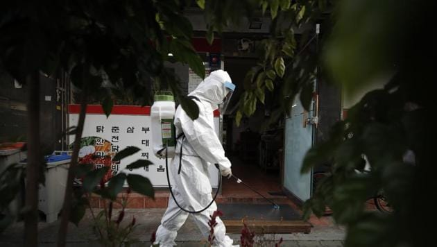 A worker in protective gear sprays disinfectant to help curb the spread of the coronavirus in Seoul, South Korea (AP Photo/Lee Jin-man)