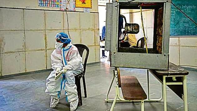 A health worker in PPE equipment cools off in front of a cooler fan at a clinic in Saket.(Amal KS/HT photo)