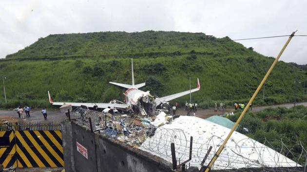 Officials stand by the debris of the Air India Express flight that skidded off a runway while landing in Kozhikode, Kerala.(AP)