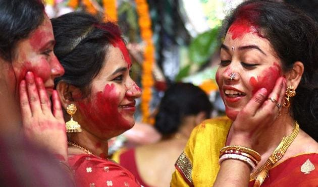 Women smearing each other with vermillion is a common sight during the sindur khela on Vijayadashami, that is the last day of Durga Puja. This year, this celebrations won't take place at most pandals in Delhi-NCR.(Photo: Arvind Yadav/HT)