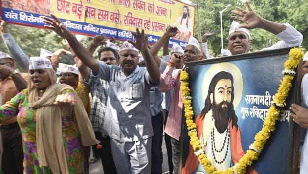 Devotees of Guru Ravidas hold his portrait and sing bhajans during a protest to demand the reconstruction of Guru Ravidas Temple at Tughlakabad and release Bhim Army activists, at Jantar Mantar, in New Delhi.(Sonu Mehta/HT PHOTO)