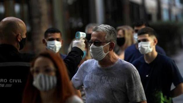 A man wearing a protective face mask has his temperature checked before entering Nova America shopping mall, as malls reopen amid the coronavirus disease (Covid-19) outbreak, in Rio de Janeiro, Brazil.(Reuters)
