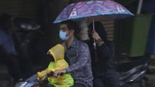 A family is seen on a motorcycle during the rain in Hyderabad. The India Meteorological Department (IMD) has issued a red alert and predicted heavy to very heavy rains in most places across Telangana till Wednesday morning.(AP Photo)