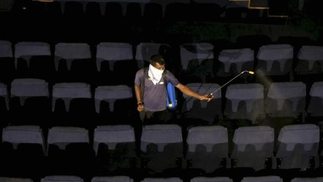 A worker sprays disinfectants on the seats of a cinema hall, after authorities allowed its re-opening with certain restrictions during Unlock 5, in Ahmedabad.(PTI)