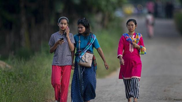 Indian tribal girls walk on a road in Umswai village, outskirts of Guwahati, India.(AP)